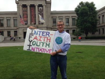 Mike, another Jewish Mentor, hold up a sign during our Inter-Faith walk for Peace, Justice and the Environment.