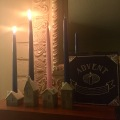 An arrangement of Advent taper candles is on a mantle in a darkened room.Two blue are lit.