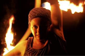 the author holds a hoop behind her, flaming wicks extend from the hoop