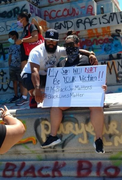 Picture of parents with sign, stating My son will not be your victim