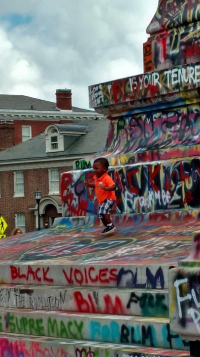 Young African-American toddler running around statue